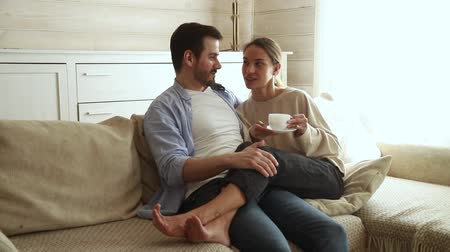 compreensão : Girlfriend holds cup drinks tea or coffee sit close to boyfriend resting together on couch talking plan day future life or vacation enjoy free weekend day, romantic relations activity at home concept Stock Footage