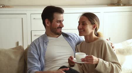 compreensão : Pretty girlfriend holds cup drink tea sitting on lap of beloved boyfriend, young family resting on couch in living room enjoy romantic dating at home chatting share dreams planning future life concept