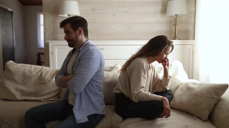 önlemek : Young man and female sitting on different sides of each other on couch and not talking keep silence. Unhappy couple boyfriend and girlfriend problems, break up, divorce, treason in relations concept Stok Video