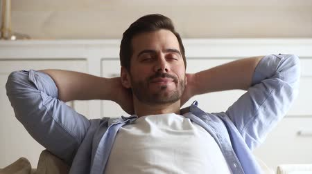 soñar despierto : Close up serene guy closed eyes put hands behind head feels tranquil keep calm take break after workday resting leaned on couch at home, no stress day nap or enjoy fresh breath air conditioner concept