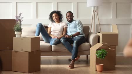 belongings : African young couple resting on couch looking at daughter son small funny active kids running holding carton boxes playing game help to mother and dad with belongings, new home relocation day concept Stock Footage