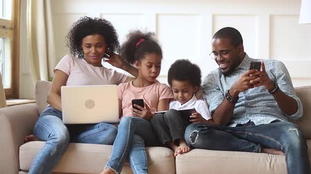 bağımlılık : African couple and little kids addicted to modern gadgets spends time together at home, afro family and children use laptops tablet computer and smartphones, dependency, bad habit modern tech concept