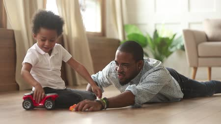 babysitter : Caring african dad and little son sitting lying on warm wooden floor with underfloor heating play with toy cars spend enjoy time together at home, modern comfy house, leisure activity with kid concept Stock Footage
