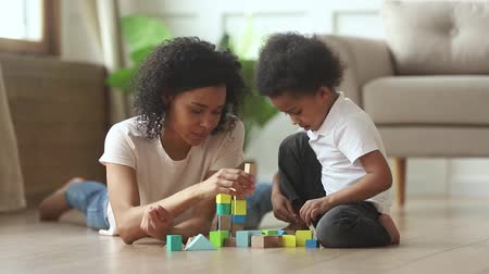 babysitter : Loving black mother little toddler son spend time at modern home sit lying on warm heated floor, building tower play with colourful toy blocks set leisure activity kid motor skill development concept