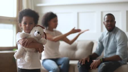 dispute : African sad little son feels afraid unhappy of parent fight, toddler kid holds embraces toy listen how mom and dad quarrelling screaming suffers from family bad relations negative atmosphere concept