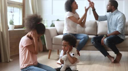 accuser : Afro frightened little kids sit on floor covered ears not to hear parents quarrel, couple sorts out relations on sofa in presence of children, negative situation affects childs mental health concept