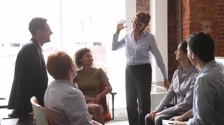 união europeia : Middle aged team leader woman boss talk motivational speech during workday, encourages before important meeting or task, express gratitude for work done gives high five to diverse staff, unity concept