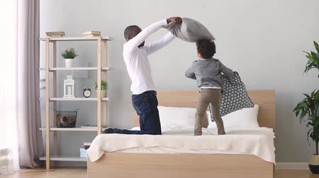 babysitter : African father enjoying pillow fight with little mixed race son on bed at home, carefree funny older younger brothers spend free time on weekend together play active game holding cushions having fun