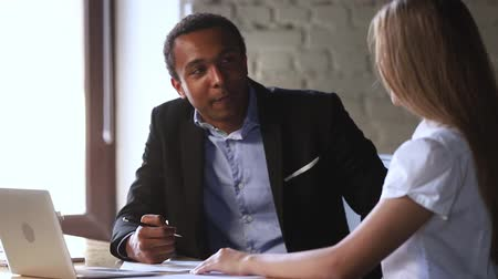 meeting negotiate : Diverse businessman and businesswoman sitting at table negotiating together in office, black boss and european woman during job interview, teammates solve common issues teamwork collaboration concept Stock Footage