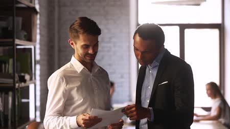 leden : Multi racial co-workers corporate members businessmen standing in co-working talking share ideas thoughts discussing financial report paperwork during busy rush working day. Teamwork paperwork concept