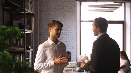 discutir : Multi-ethnic businessmen talking having informal conversation good relations take break during workday chatting discuss common tasks in co-working office, multi racial co-workers friendship concept Stock Footage