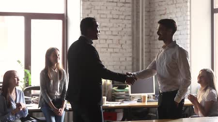 accepting : African boss congratulates successful male worker of month with promotion talk words of praising, staff applauding executive manager greets company client handshake welcomes him during meet in office