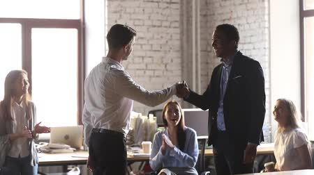 leden : Caucasian boss congratulating african male worker with promotion shaking hands express gratitude appreciating for good work result, black employee getting praise from ceo while colleagues applauding