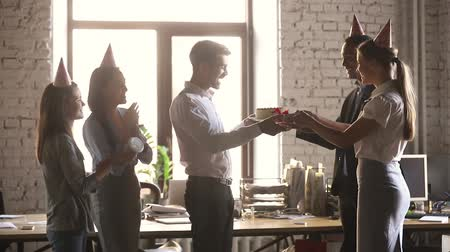 agradecido : Man get from co-workers birthday cake blow candle feels gratitude, staff wearing party hats congratulating colleague presents a gift box clap hands cheering express respect and warm relation concept Archivo de Video