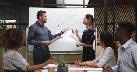 lecture : Two happy multiethnic conference speakers presenters team work together give presentation on whiteboard explain corporate project strategy training workers group at office workshop meeting concept