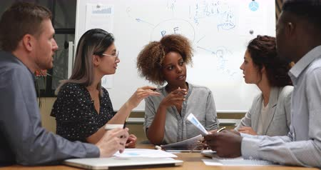 поощрение : Diverse business people corporate work group discussing project strategy sharing ideas sit at conference table, multiracial professional team staff brainstorming planning teamwork at office briefing