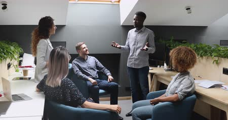 brifing : Confident african american business leader boss mentor speak to happy multiracial team people gather in modern office instructing motivating workers explain project plan at corporate meeting training Stok Video