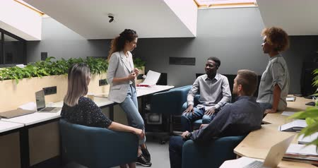 brifing : Confident young caucasian businesswoman company leader speaking to diverse staff team people at corporate training teaching explaining project at informal corporate briefing in modern office room Stok Video