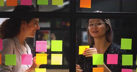 samolepky : Happy friendly diverse female colleagues talking working with sticky notes, smiling professional team two businesswomen sharing creative ideas replacing stickers planning project write on glass wall