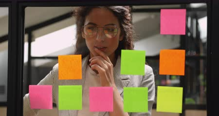 samolepky : Focused young business woman think of project strategy attach replace stick notes on glass board, female corporate leader coach planning organize work on stickers on scrum glass window wall