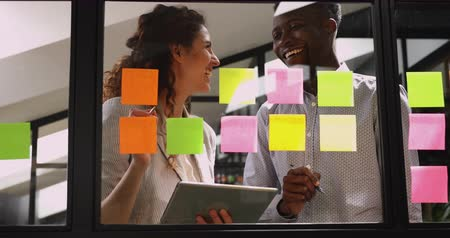 samolepky : Two smiling friendly team people talking planning work on sticky notes, happy african male and caucasian female colleagues write creative ideas on post it stickers glass wall brainstorming on project Dostupné videozáznamy