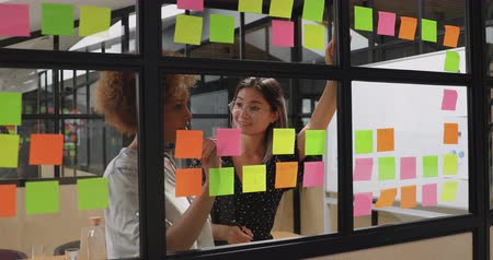 brifing : Happy smiling diverse female coworkers students team african and asian businesswomen talking working in teamwork write creative ideas research tasks on sticky notes stand behind glass wall Stok Video