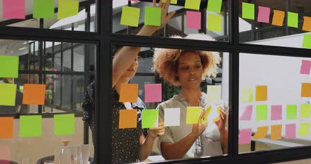 samolepky : Two african and asian businesswomen talk work together in teamwork share creative ideas discuss project plan replace  sticky note stand behind glass discuss corporate strategy at team briefing Dostupné videozáznamy