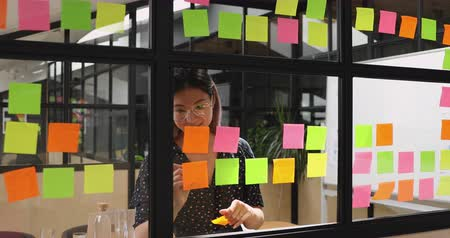 samolepky : Happy young asian businesswoman teacher leader write tasks creative ideas on stick notes replace attach stickers on glass wall planning project corporate strategy on scrum office board
