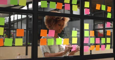 poczta : Focused young african female professional student worker coach write ideas replacing post it sticky notes with done research tasks planning project strategy on glass scrum board wall in modern office