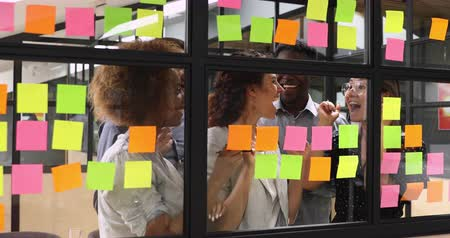 colaboração : Happy overjoyed multiracial business team people group stand behind glass wall sticky notes celebrate corporate success victory good work result concept feel excited finished project job well done