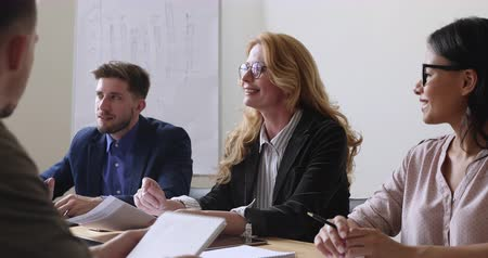 meeting negotiate : Smiling older mature female leader consulting clients about contract deal benefits, middle aged businesswoman mentor executive conduct corporate briefing teaching diverse team sit at office table Stock Footage