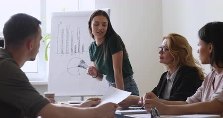 flipover : Young female project manager leader conduct team meeting in boardroom explaining diverse work group people new sales strategy speaking teaching multiethnic staff during corporate briefing training Stockvideo