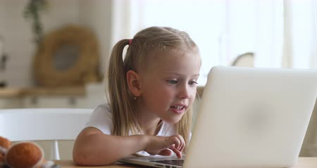 addicted : Curious cute little kid girl using laptop alone, smart preschool child learning computer online surfing internet without parental control at home, children education technology addiction concept