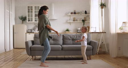 den matek : Funny cute small kid daughter copy imitate carefree young mom dancing together at home, happy family single mother and active little child girl having fun enjoy funny dance in modern kitchen interior