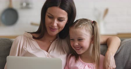 サーフィン : Happy parent mother and cute small kid daughter laughing using laptop at home watching funny social media videos make video call browsing internet looking at notebook screen having fun relax on sofa 動画素材