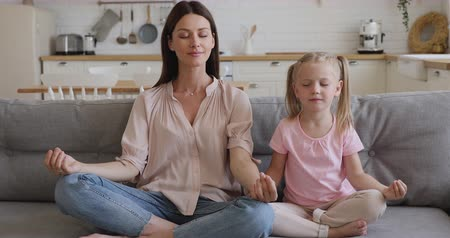 respiração : Healthy happy family young mindful mom teaching cute little kid daughter learning doing yoga exercise together with eyes closed sit on sofa in kitchen, mother and child laughing meditating at home