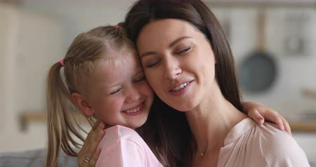 foster : Affectionate happy family single mom and cute little child daughter laughing embracing bonding with eyes closed together, young mother foster parent hug small kid girl cuddling touching noses at home Stock Footage