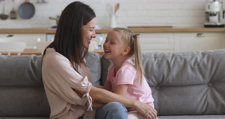 детский сад : Happy playful family young mom and cute small kid daughter tickling playing laughing relaxing sit on sofa at home, smiling mother having fun with little child bonding together on kitchen couch