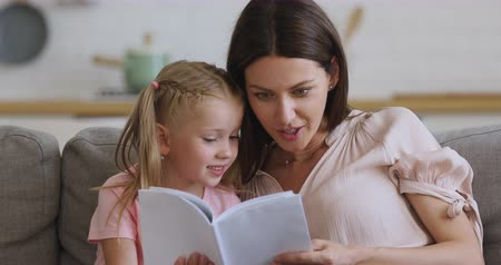 babysitter : Happy family mom and cute kid daughter having fun with book sit on sofa, smiling mother teaching little girl learning reading telling fairy tale story, parent with child educational activity at home