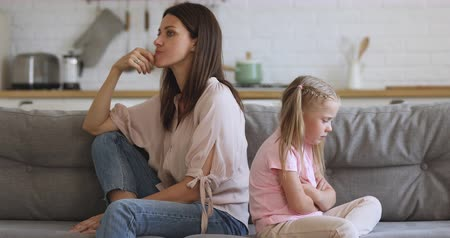 аргумент : Upset stubborn young mother and little child girl sit turn back on sofa not talking after fight argument, offended kid preschool daughter ignore worried sad mom, parents and children conflict concept