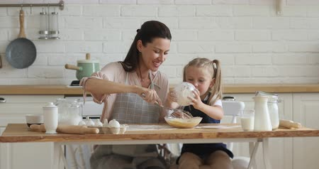 den matek : Happy family young mom and cute little child daughter beating dough mixing eggs and flour in modern kitchen, small kid girl helping mum cooking together preparing cake or cookies on mothers day