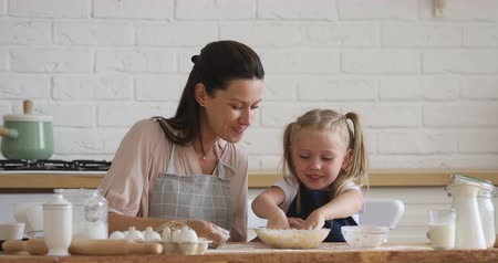 mateřská škola : Cute small kid daughter learning kneading dough with hands helping mom in modern kitchen, happy family adult mother and little child girl prepare cookies biscuit having fun cooking together at home Dostupné videozáznamy