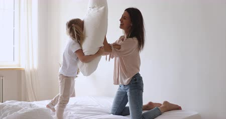 nanny holding : Happy active family mom and little child girl enjoy funny pillow fight on bed, smiling mother with small cute kid daughter having fun together playing laughing in bedroom together in the morning Stock Footage
