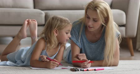 puericultura : Cute smart preschool child daughter learning drawing with felt pen coloring picture talk enjoy creative activity with young mom or babysitter helping little kid girl lying on floor playing at home. Stock Footage