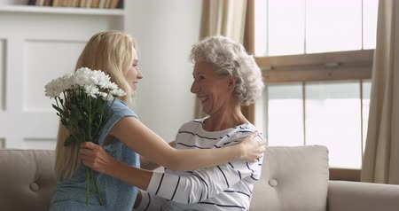 blahopřání : Adult daughter presenting flowers congratulating hugging old mature mom with mothers day concept, young woman embracing happy senior retired mum looking at camera bonding together at home, portrait