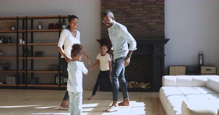 taniec : Happy carefree family young african parents mom dad and cute little children kids boy and girl dancing in circle clapping hands playing having fun enjoying funny activity game in modern living room. Wideo