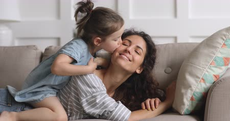 acariciando : Cute adorable funny little kid daughter tickling caressing young mum kissing on cheek playing on sofa at home, happy family mother and small child girl wear crown enjoying bonding having fun on couch Vídeos