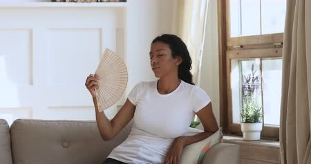 perspiring : Overheated annoyed african woman feel hot use waving fan tired of high temperature sit on sofa at home, stressed young lady sweating suffer from summer weather heat problem without no air conditioner