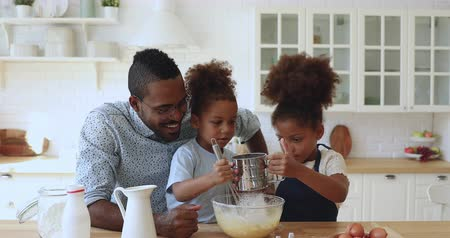 fırçalamak : Cute african american family young father dad with mixed race little children kids siblings preparing dough together whisking flour and eggs having fun cooking baking cake cookies in modern kitchen Stok Video