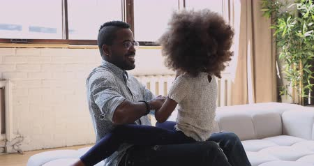 bağ : Happy family african dad and little funny kid daughter having fun together at home, smiling father laugh play with cute small child girl dance sit on sofa bonding enjoy lifestyle game in living room